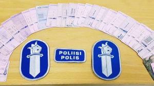 Rad av körkort som beslagtagits av polisen och i mitten polisens emblem.