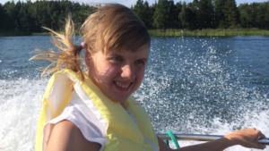 Ung kvinna med gul flytväst ler. Hon åker båt en varm sommardag.