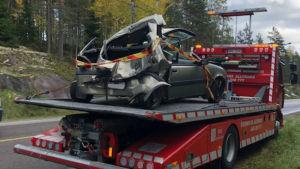 Bil som bogseras bort från olycksplats. Bakre delen av bilen förstörd.