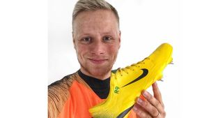 En man iklädd en orange fotbollströja. Visar upp en gul fotbollssko och ser glad ut.