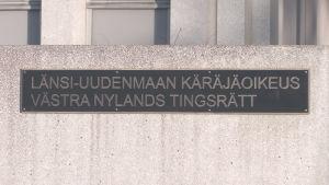 En skylt på en mur där det står Västra Nylands tingsrätt på svenska och finska.