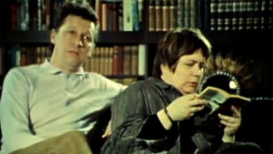 Pariskunta (Veijo Pasanen ja Ritva Valkama) istuu sohvalla, mies haaveilee autoilusta, nainen lukee kirjaa (1978).