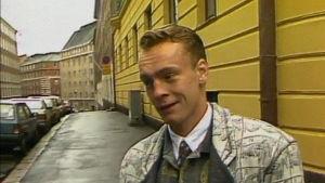 Juppi-kulttuurista kertovassa ohjelmassa Lauri Nykopp haastattelussa. 1980-luvun vaatteet yllään.