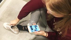 tyttö laittaa kenkiä jalkaan ja selaa samalla Instagramia