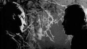 Nainen ja mies katsovat toisiaan hämärässä
