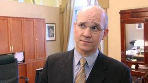 En medelålders man i kostym står i ett arbetsrum.