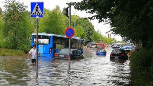 En man vadar i knähögt vatten. Bakom honom syns bussar och bilar som kör genom vattenmassorna.