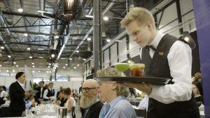 Johan Lindström serverar mat på Mästare-tävlingen.