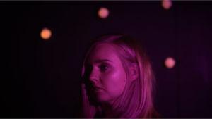 Vaaleahiuksisen naisen pää keskellä pimeyttä, muutama valo näkyy taustalla. Kasvoihin heijastuu violetti valo.