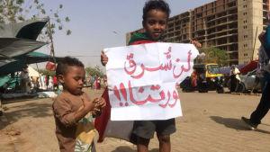 """Stjäl inte vår revolution"", står det på det plakat som en liten sudanesisk pojke håller upp under de fortsatta protestern i Khartoum fredagen den 12 april"