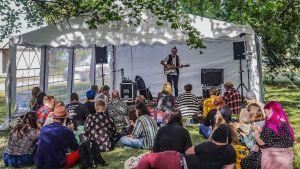Ulkona teltassa mies soittaa kitaraa ja laulaa, edessä nurmikolla istuu ihmisiä katsomassa