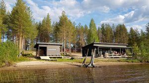 Kaksi saunarakennusta järven rannalla