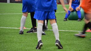 Barns ben och fötter som spelar fotboll.