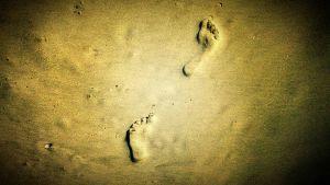 Ihmisen jalanjälki rantahiekassa