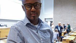 Abdirahim Hussein på bild med hängsnara och hotbrev som skickats till honom på Helsingfors stadsfullmäktige.