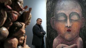 taitelija nojaa taidemuseossa seinään ja vieressä suuri puusta tehty reliefi