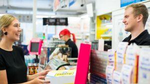 Ung kvinna ger ett Ärräpaket över disken till R-kioskens personal
