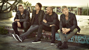 Fyra män klädda i mörka färger och läderrockar sitter i en urban miljö tillsammans.