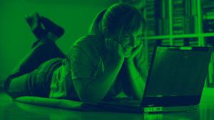 Kvinna ler framför en bärbar dator.