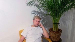 Dj-muusikko Epix viherkasvin vieressä valkoista taustaa vasten.