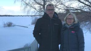 En man och en kvinna med vinterjackor på stårt i ett vinterklätt landskap. I bakgrunden syns bron över Torneälv.