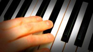 pianon koskettimisto ja käsi lähikuvassa