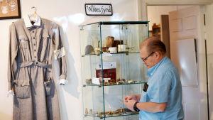 """En man står och håller i ett föremål från en monter med saker som finns utställda på ett museum. Ovanför montern står det """"Wibbes hörna""""."""