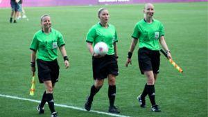 Tonja Wecsktröm, Kirsi Heikkinen och Anu Jokela går bredvid varandra invid en fotbollsplan.