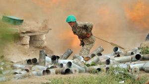 En soldat står bakom en kanon omgiven av tomhylsor och krutrök.