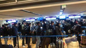 En stor grupp asiatiska resenärer med munskydd på flygplats.