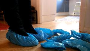 Asuntonäytöstä lähikuva jaloista, joissa kenkäsuojat. Lattialla lisää sinisiä kenkäsuojia.