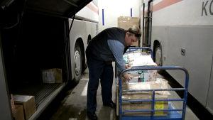 busschaufför lastar paket från en vagn in i en buss.
