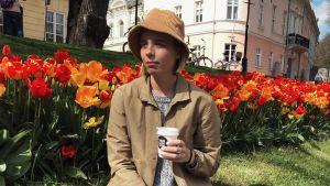 En kvinna sitter i en park. I bakgrunden syns en rad med tulpaner. Hon håller i en kopp kaffe.