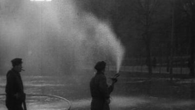 Män sprutar vatten på skridskoplan, 1933