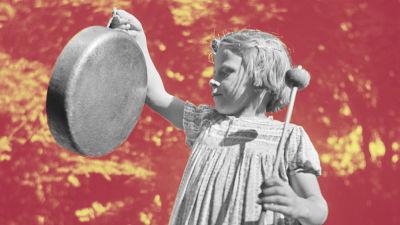 En flicka som slår på en gonggong.