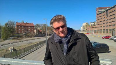 Mies seisoo sillalla radan varrella, taustalla tiilirakennus.