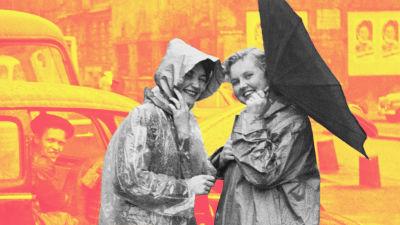 Två kvinnor poserar till kameran i regnkläder och ett vänt paraply i Hamburg.