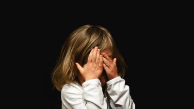 Pieni tyttö peittää kasvonsa.