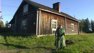 puutalon edustalla vanha nainen nojaa keppiin