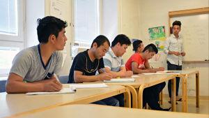 En ung invandrare lär ut finska till andra invandrare i ett klassrum.