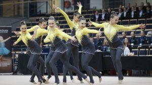 En grupp unga kvinnor i gul-grå gymnastikdräkter står i olika positioner