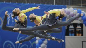 Tre unga kvinnor i gul-grå gymnastikdräkter gör spagat i luften