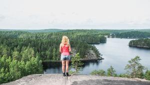 En kvinna iklädd shorts och ett rosa linne står på en bergskant och blickar ut över en sjö och skog i Finland. Det ser mycket fridfullt ut.