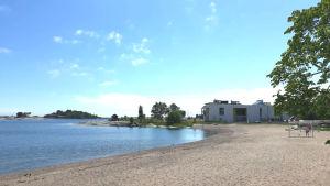 En sandstrand och en vit byggnad i bakgrunden.