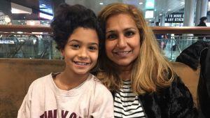mor och dotter ler in i kameran på flygplats