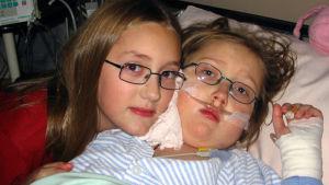 Två barn som ligger i en sjukhussäng. Det ena barnet har bandage på handen och syrgasslang i näsan.