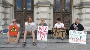Unga klimataktivister sitter på en trappa med skyltar.