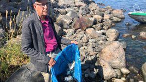 En äldre man, Folke Österman står på en stenig strand. I hans händer är en stor kasse med plastskräp.