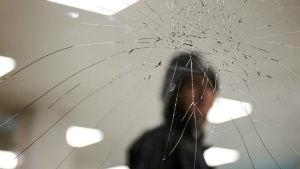 Kvinna bakom krossad glasruta