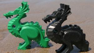 Två legodrakar, en grön och en svart, på en sandstrand.